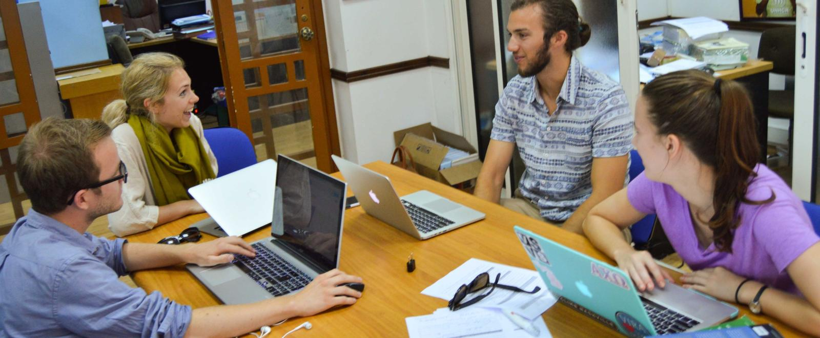 A group of Human Rights interns in Africa have a lively discussion while doing research for a case.